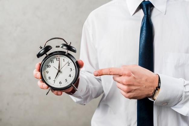 灰色の壁に対して時間に指を指している実業家のクローズアップ