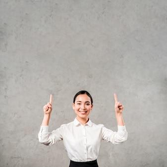 灰色の壁に対して彼女の指を上向きに指している笑顔の若い実業家の幸せな肖像画