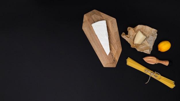 台所のテーブルの上の木製のジューサーと調理のイタリアパスタ成分
