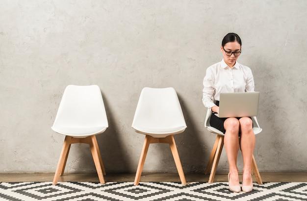 ノートパソコンで入力する椅子に座っているアジアの深刻な若い実業家