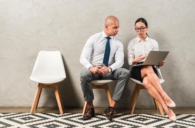 Бизнесмен и коммерсантка сидя на стуле обсуждая что-то используя компьтер-книжку