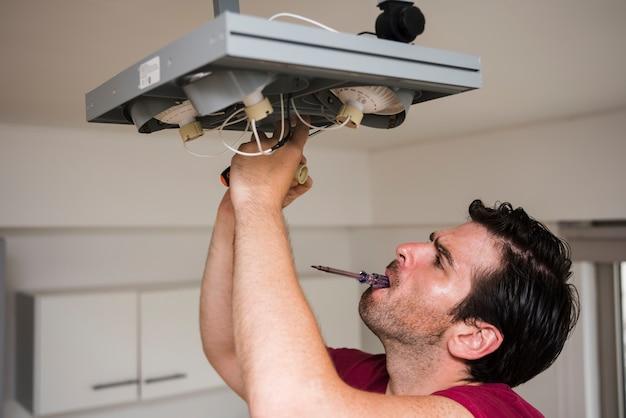 自宅で天井のフォーカスライトを修復しながら口の中でテスターを運ぶ男