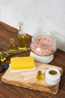 ヒマラヤの塩の瓶の俯瞰。ハーブ石鹸最後の一つ;エッセンシャルオイル;テーブルの上に蜂蜜とリモニウムの花