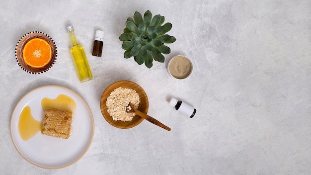ハニカムオーツ麦;エッセンシャルオイル;サボテンの植物。ラッスール粘土。白いコンクリートのテクスチャ背景に半分の柑橘系の果物