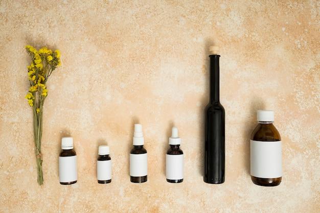 ベージュ色のテクスチャ背景にエッセンシャルオイルのボトルの行を持つ黄色のリモニウムの花