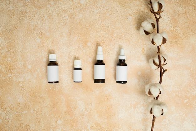 ベージュ色のテクスチャ背景のエッセンシャルオイルのボトルの種類と綿の枝