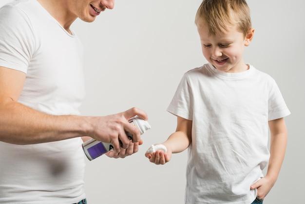 彼の息子の白い背景で隔離の手にシェービングフォームをスプレー父親のクローズアップ