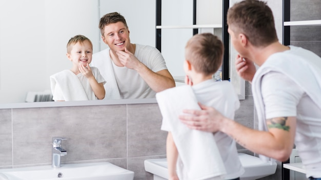 父と息子の手で彼らのあごに触れる鏡で見ています。