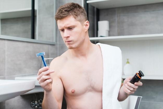 魅力的な若い男が浴室で電気トリマーを持って青いかみそりを見て