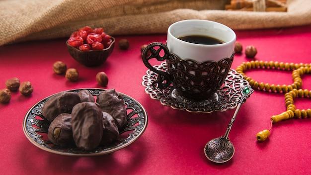 日付のフルーツとビーズのテーブルの上のコーヒーカップ