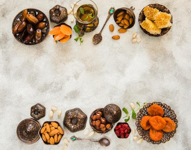 Стакан чая с разными сухофруктами и орехами