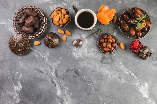 Кофейная чашка с финиками, фруктами и орехами