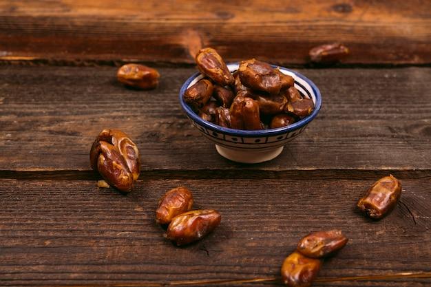 木製のテーブルの上にボウルにフルーツの日付