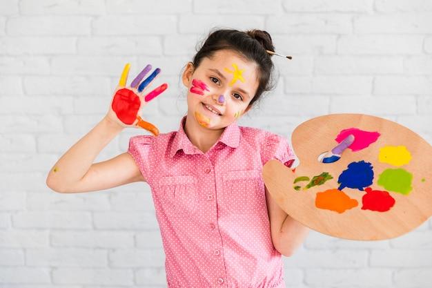 Портрет девушки, показывая ее окрашенные руки, держа разноцветные палитры