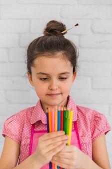 色とりどりの鉛筆を手で見ている少女の肖像画