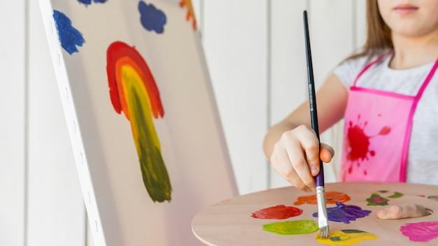 キャンバスにペイントブラシで絵を描く少女のクローズアップ