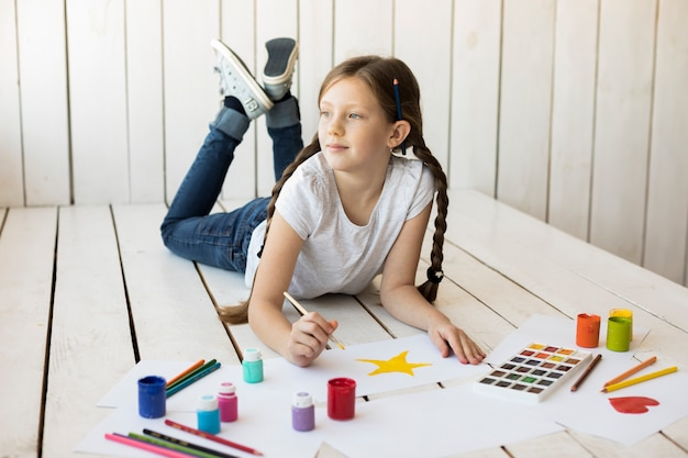 絵筆で床の絵星の上に横たわる美しい少女