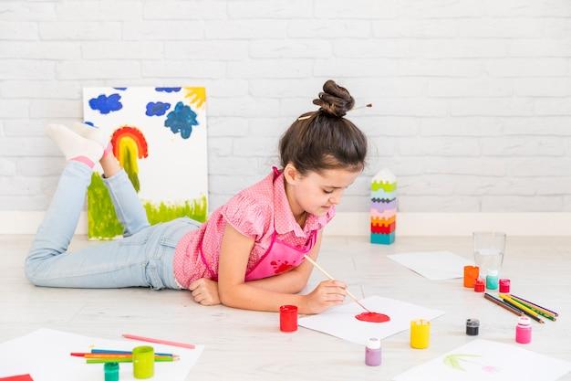 ブラシで白い紙の上の床の絵の上に横たわる少女