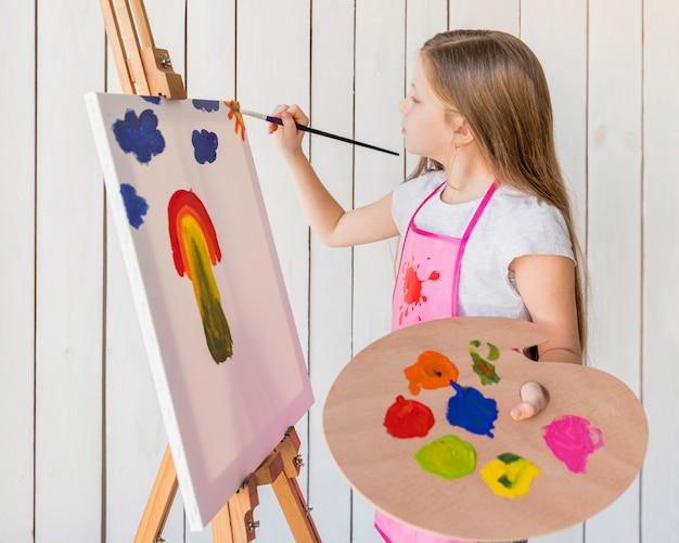 ペイントブラシでイーゼルに手書きでパレットを保持している女の子のクローズアップ