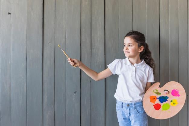 ペイントブラシとパレットを手で保持している灰色の木製の壁に対して少女の肖像画を笑顔