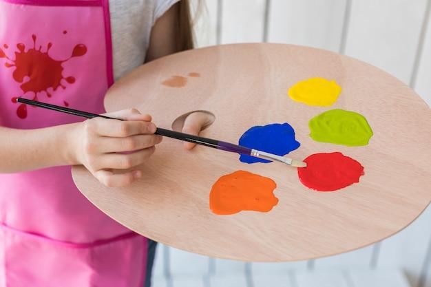 木製パレットの上にブラシで塗料を混合する女の子のクローズアップ