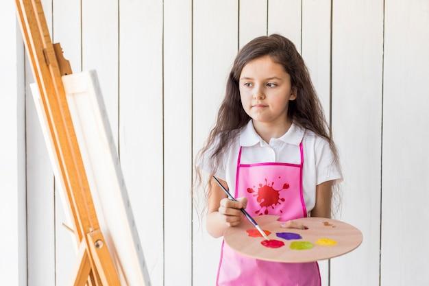 キャンバスを見て木製のパレットの上にブラシで塗料を混合する女の子のクローズアップ