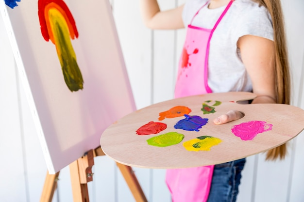 色とりどりの木製パレットを手で押しキャンバスに絵の少女のクローズアップ
