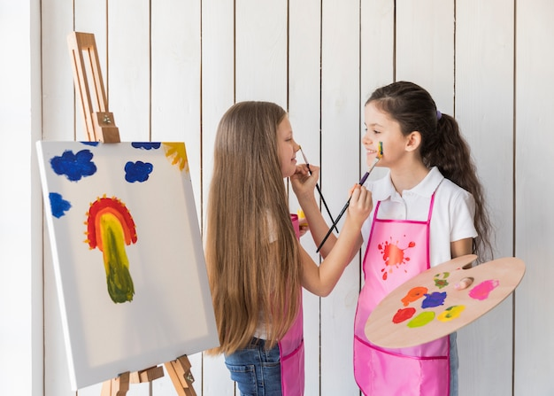Улыбающиеся две девушки рисуют друг друга лицом с кистью, стоя возле холста