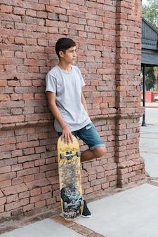 Подросток, опираясь на кирпичной стене, держа скейтбординг, глядя