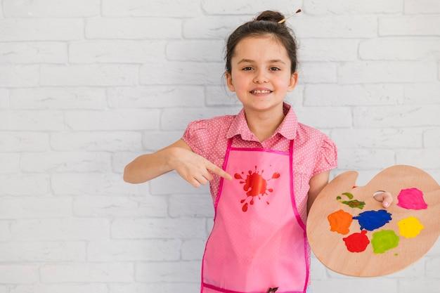 Улыбающаяся маленькая девочка, стоящая перед белой кирпичной стеной, указывающая на красочную палитру в руке