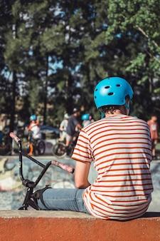 屋外に座って自転車で青いヘルメットをかぶっている男の子の背面図