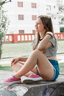 音楽を聴く公園に座っているファッショナブルな微笑の女の子