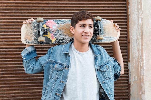 スケートボードを持って外に立っている少年を考えています