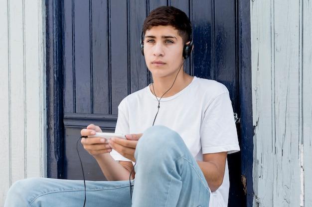考えている少年が携帯電話で音楽を聴く