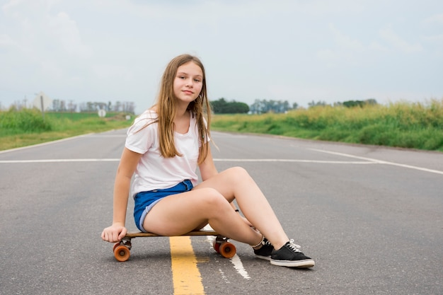 空の道でスケートボードの上に座ってモダンな魅力的なかわいい女の子