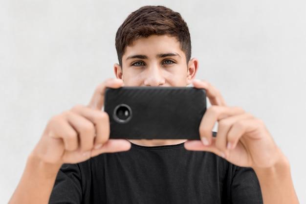 白い背景に対して携帯電話を通して写真を撮る少年のクローズアップ