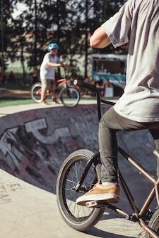 Вид сзади мальчика, практикующего езда на велосипеде в скейт-парк
