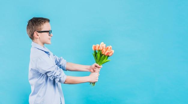 青い背景に対して新鮮なチューリップを与える眼鏡を身に着けている男の子の側面図