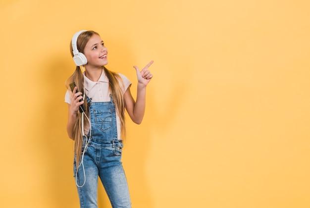 黄色の背景に対して何かを指しているヘッドフォンで音楽を聴いている女の子の肖像画を笑顔