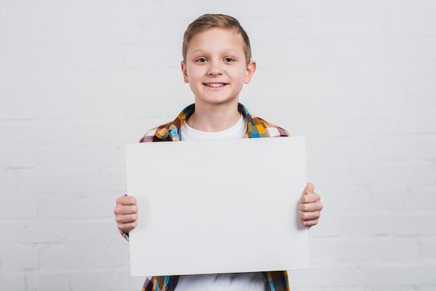 白い空白プラカードを示す白い壁に立っている幸せな少年の肖像画
