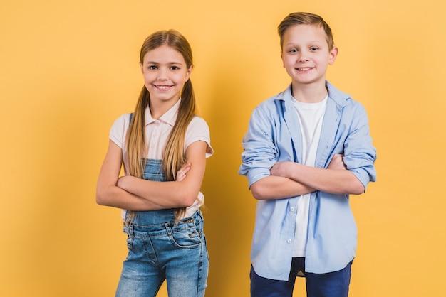 Портрет счастливый милый мальчик и девочка со скрещенными руками, глядя в камеру