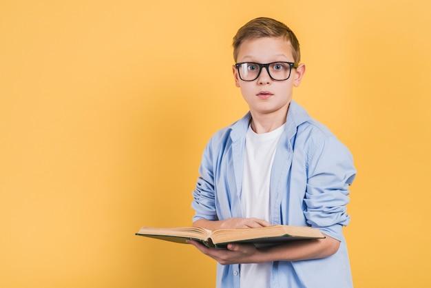 黄色の背景に対してカメラを探して手に開いた本を持って眼鏡をかけている深刻な少年