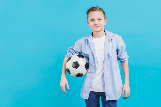 青い空を背景に立っているカメラを探しているサッカーボールを持つ男の子の肖像画