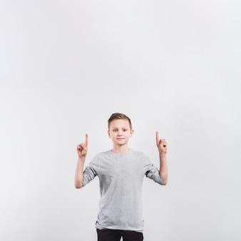 灰色の背景に分離されたカメラを上向きに彼の指を指している微笑む少年