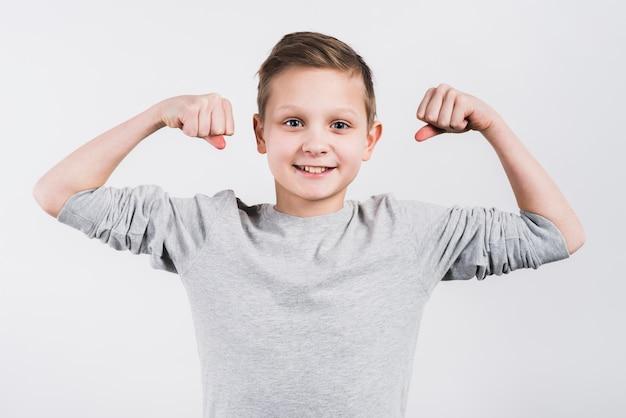 灰色の背景に対してカメラの地位を探して彼の拳を噛みしめて微笑む少年の肖像画