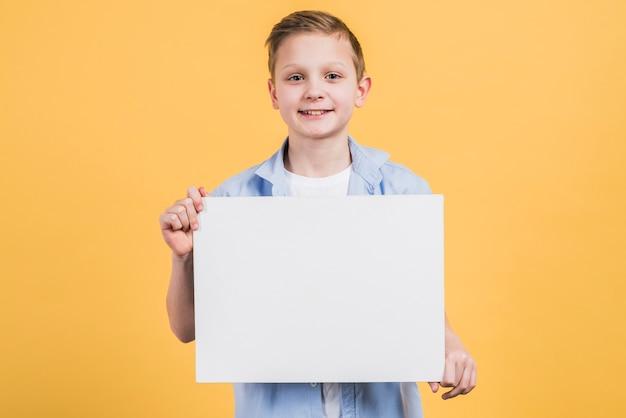 黄色の背景に対して白い空白プラカードを示すカメラを探して微笑む少年の肖像画