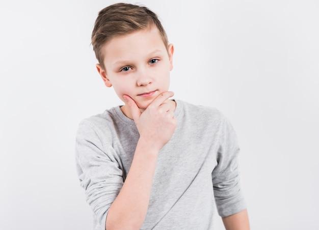 Задумчивый мальчик с рукой на подбородке смотрит в камеру на белом фоне