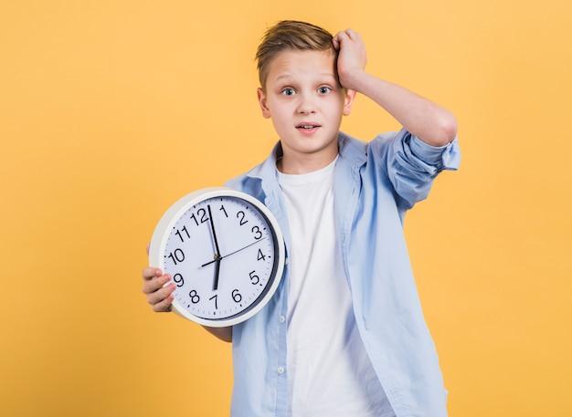 黄色の背景に対して白い時計立って保持している彼の頭の上の手で心配している少年