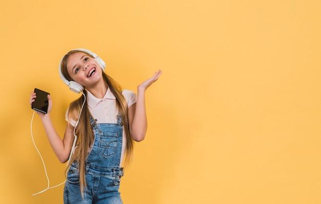 Портрет девушки прослушивания музыки на наушники, стоя на желтом фоне