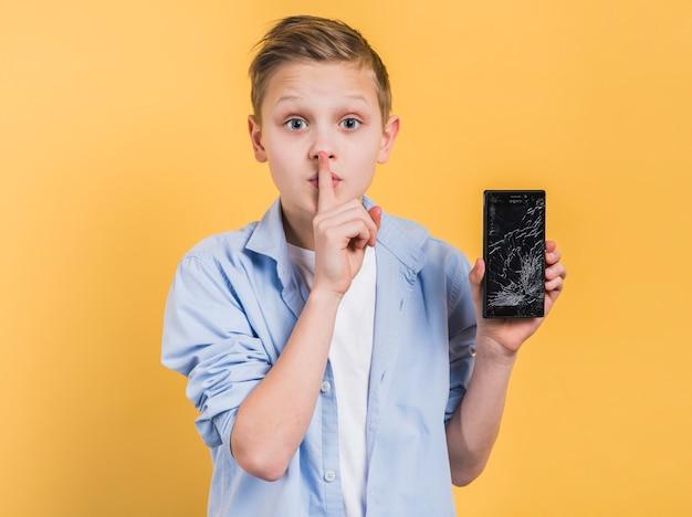 Мальчик с пальцем на губах показывает разбитое стекло смартфона на желтом фоне